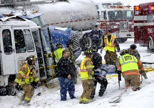 Members of the Springfield and Harmony Fire Departments rescue one of several victims trapped in a bus from the Creative Learning Workshop Thursday, Jan. 7 on Interstate 70. The bus collided head-on with a semi-truck carrying a tanker trailer. Four people killed. CNN photo by Bill Lackey
