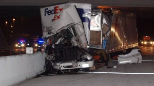 The wrecked FedEx truck is shown leaning against the outside barrier wall of the interstate.