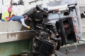 The cab of the truck and part of the trailer dangled precariously over the edge, directly above Broadway Avenue.