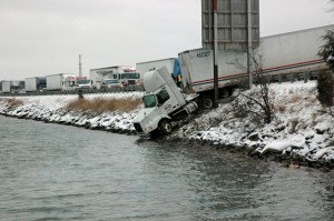 The cab of the tractor trailer dangled off the bridge edge, a few feet from the cold water.