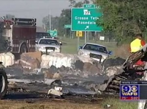 The burned wreckage of a sport utility vehicle and two 18-wheelers after a fiery crash that took the lives of four people Friday morning on I-10 just east of Grosse Tete, Louisiana.