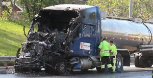 According to an Illinois State trooper at the scene, as the truck driver was changing lanes he lost control of his rig and slid into the path of another semi tanker truck that was already in the right lane of the interstate.