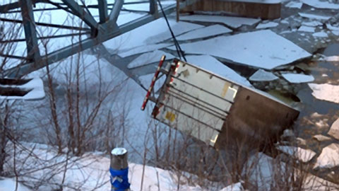 Work crews pull a semi trailer from icy Red Cedar River in Menomonie, WI after an 18 wheeler plunged into the river cab-first, killing the driver. Rescue crews were still searching for a passenger who was in the big rig at the time. Photo credit: WEAU-TV