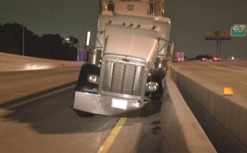 A pedestrian walking on the freeway caused a semi truck driver to swerve and crash into the concrete median barrier in Houston, TX on May 22, 2013. Photo credit: KHOU.com