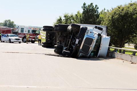 A semi truck overturned after rounding a curve at the U.S. Highway 287 / I-35E interchange in Waxahachie, TX on October 8, 2013. Photo credit: Andrew Branca / Waxahachie Daily Light